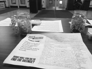 The Day of Silence sign-up sheet with the names of those who participated and a jar of purple ribbons that symbolize the Day of Silence
